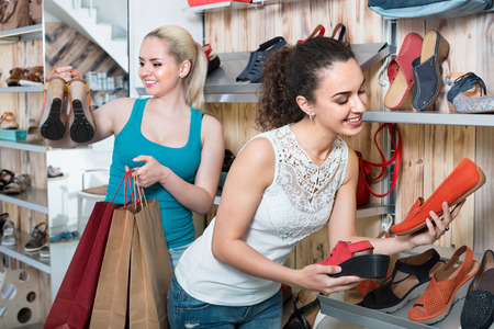 desires 25: Two satisfied young girls holding a paper shopping bags in the boutique Stock Photo