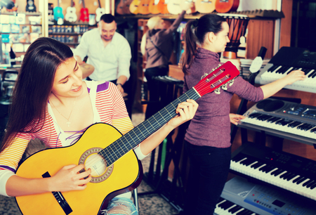 synthesiser: Positive people looking at professional musical instruments in store