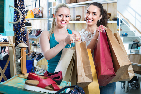 Two beautiful happy  girls holding a paper shopping bags in the boutique Stock Photo