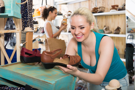desires 25: Portrait girl choosing a pair of shoes while other customer still  looking Stock Photo