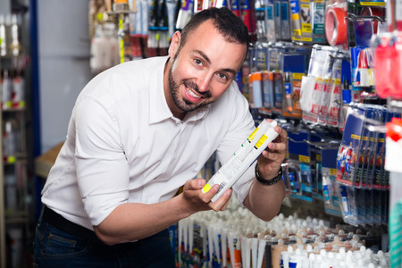 sealant: Portrait of smiling man selecting sealant bottle in household department