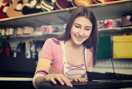 Teenage girl choosing synthesizer in music instruments shop