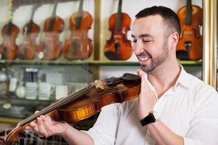 Cheerful man with beard purchasing traditional violins in store