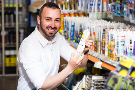 sealing: adult man picking sealing component in household shop Stock Photo