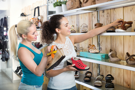 desires 25: Ttwo glad beautiful young women selecting shoes and chatting among the shelves. Focus on both persons