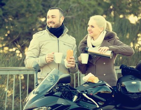 sandwitch: Young smiling couple drinking coffee and chatting near motorcycle