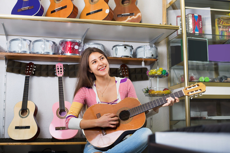 happines: Smiling teenage girl posing with classical guitar in shop