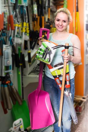 Porträt der amerikanischen Frau Gartenarbeitausrüstung in der Haushaltsabteilung vorwählend