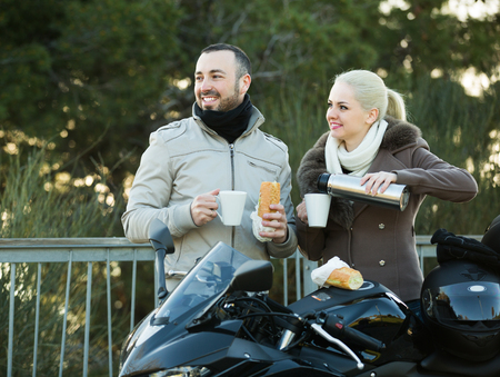 Young smiling couple drinking coffee and chatting near motorcycle