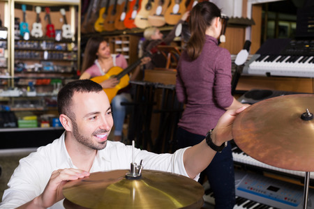 synthesiser: Different people looking at professional musical instruments in store Stock Photo