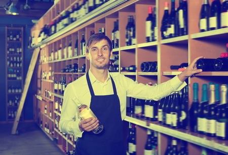 promoting: Laughing seller man wearing apron promoting bottle of wine in wine store