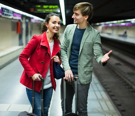 Happy young couple standing at underground station awaiting the train. Focus on women Stock Photo
