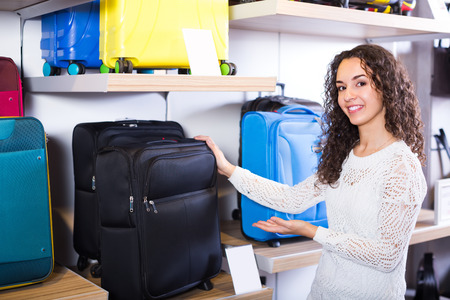 handy: Cheerful smiling young brunette selecting handy trunk in store Stock Photo