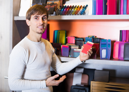 faux: Happy young man choosing faux leather wallet in store Stock Photo