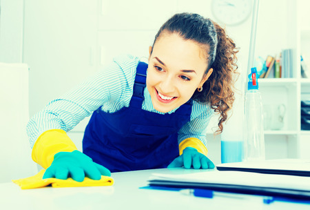joyful female professional cleaner in working overall  dusting in modern office