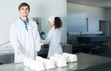 technologists: Two joyful young technologists in lab coats during production process at dairy farm lab