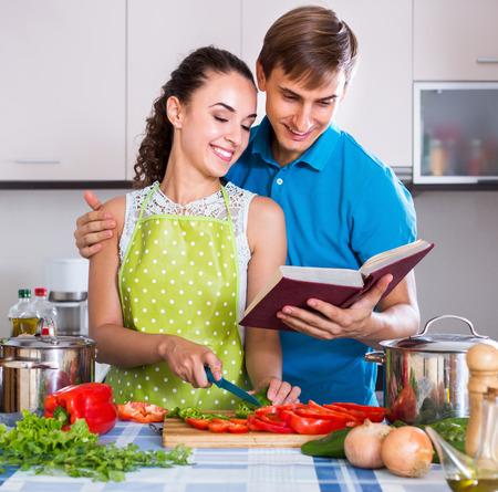 vegeterian: Smiling woman and boyfriend with cookbook preparing vegeterian soup