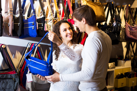 shopgirl: Cheerful female shopgirl helping young man to select handbag in store