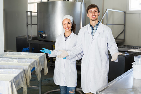lab coats: Two smiling workers in lab coats showing their production process at dairy farm lab