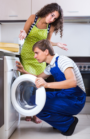 serviceman: Serviceman checking washing machine at the kitchen of young female client