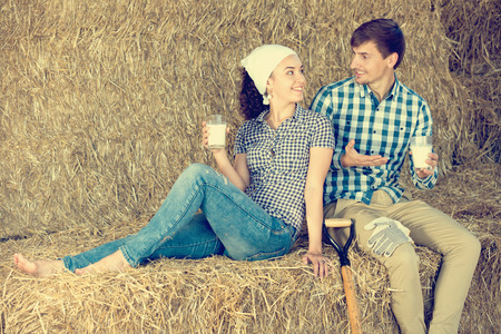 25 35: smiling young man and woman chatting and enjoying fresh milk in the hay Stock Photo