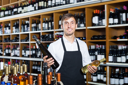 promoting: Smiling seller man wearing apron promoting bottle of wine in wine store