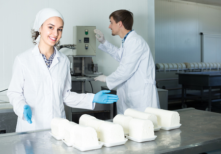 lab coats: Two positive technologists in lab coats showing their production process at dairy farm lab Stock Photo