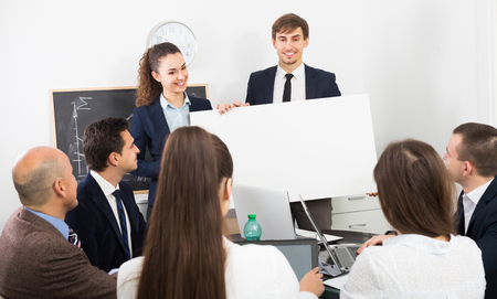 new products: Positive people presenting new products plan at poster during conference  indoors Stock Photo
