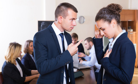 severely: Manager lecturing upset team member severely at office meeting