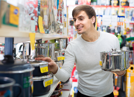 stockpot: Young male customer choosing stockpot in household store and smiling Stock Photo