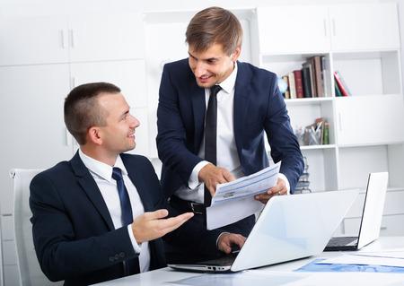 formalwear: two joyful male business colleagues in formalwear working together using laptops in company office Stock Photo