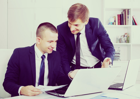 formalwear: two smiling business male assistants wearing formalwear working together using laptops in company office