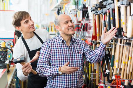 25s: Ordinary positive smiling customer and seller choosing hammer in household store Stock Photo