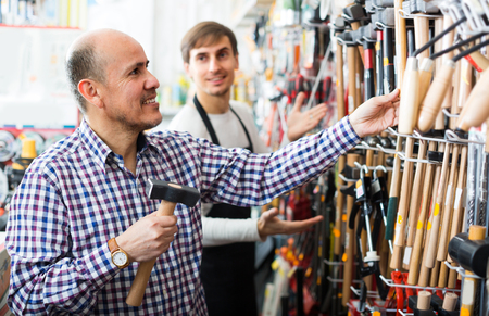 tooling: Male client and professional salesman at tooling section in building store Stock Photo