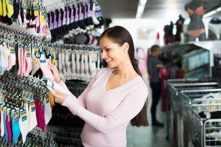 hilarious: Hilarious young woman choosing pair of socks in clothes shop