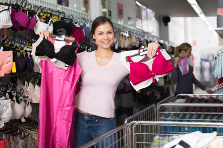 Positive woman shopping lace uplifts and panties in lingerie department
