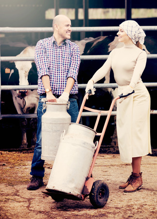 look latino: Positive man and woman farmer workers standing with big milk buckets and talking in cowshed. Focus on man Stock Photo