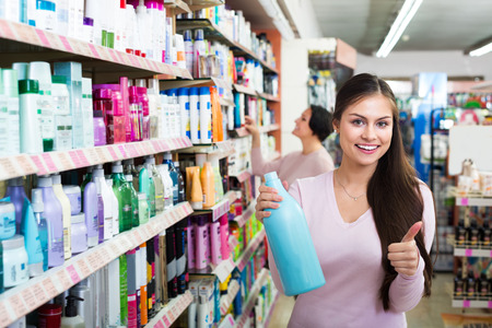 consuming: Portrait of happy young girl and mature woman choosing shampoo in beauty department