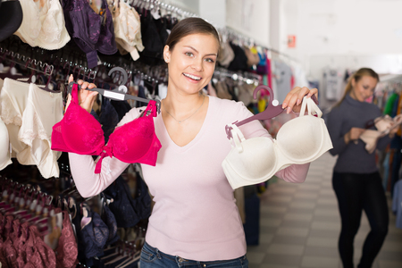silky lingerie: Positive woman holding different brassiere in hands in underwear store