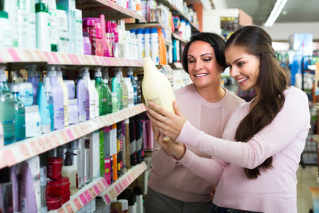 haircare: Two smiling female customers selecting haircare products in drugstore . Selective focus Stock Photo