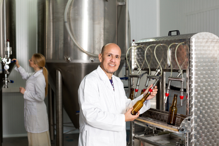 glad: Glad man employee bottling beer in glass bottles on modern facility