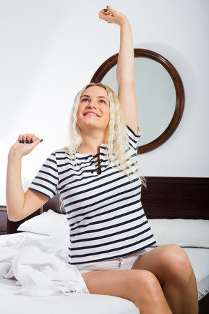 awaking: Young woman with long hair awaking in bedroom