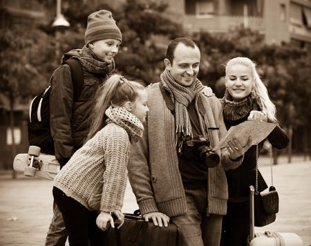 clase media: familia de clase media de cuatro miembros feliz el control de la dirección en un mapa