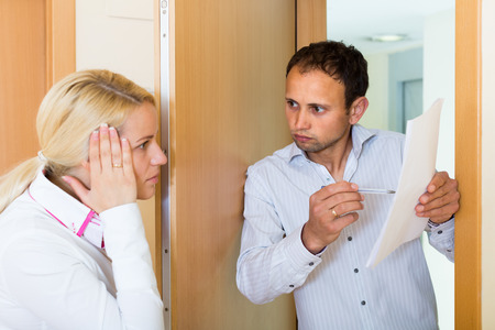 confiscation: Collector is trying to get the arrears from woman at home door Stock Photo