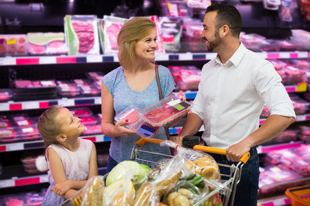 refrigerated: smiling european parents with daughter choosing meat in refrigerated section in hypermarket Stock Photo