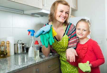 tidy: Portrait of smiling girl and mom tidy up at home kitchen Stock Photo