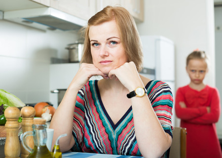 Adult frustrated mom scolding little daughter at home