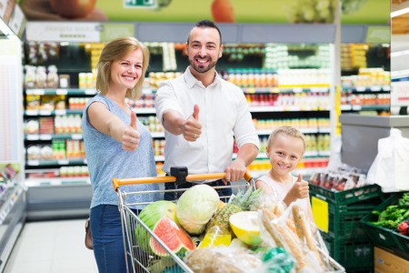 Cheerful man and woman with daughter holding shopping trolley with good in store Stock Photo