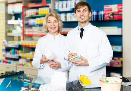 dispensary: Female pharmacist and pharmacy technician posing in drugstore Stock Photo
