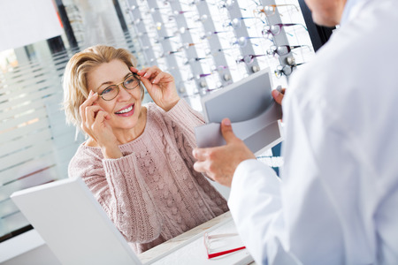 Mature ophthalmologist and female pensioner choosing a glasses at the optics store